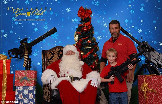 Family fun: A gun-toting youngster poses alongside Santa at a Christmas photo shoot in Scottsdale, Arizona