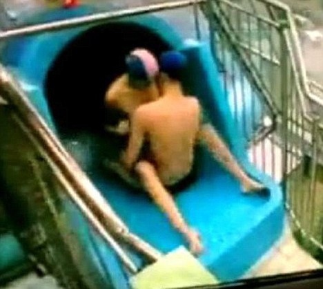Tunnel of love: The naughty couple are caught on CCTV on top of the waterslide in Poland