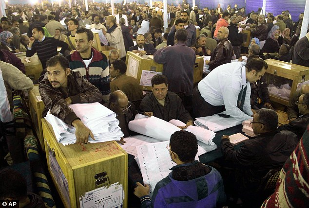 Democracy in action: Men wade though votes cast in the second round of the country's parliamentary election