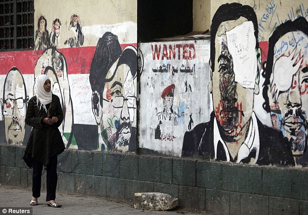 Sign of the times: A girl looks at recent graffiti depicting protesters with eye injuries