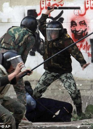 No mercy: Egyptian army soldiers beat and arrest a woman in a niqab in Tahrir Square