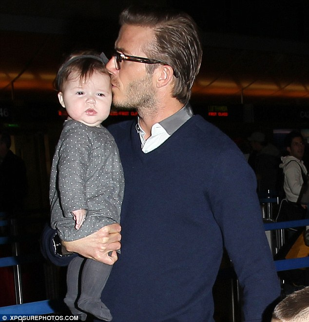 Daddy's girl: David plants a kiss on Harper as they head to check in for their flight