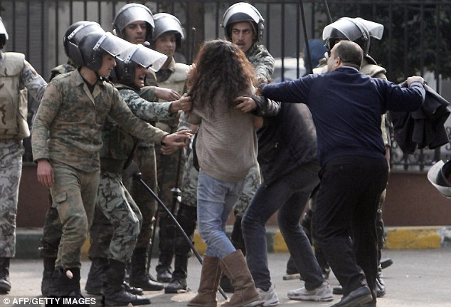 Man-handled: Egyptian soldiers clash with this female protester and two male protestors near Cairo's Tahrir Square