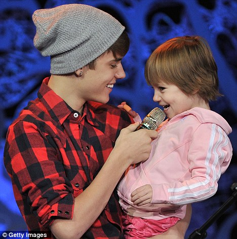 Family time: Justin Bieber takes his little sister Jazmyn up on stage with him as he performs at a homecoming convert in Massey Hall, Canada, yesterday
