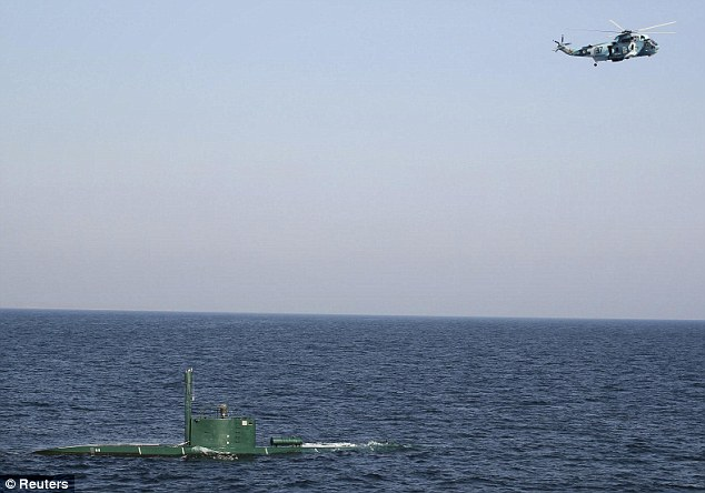 Tensions: A military helicopter flies over a submarine during the Velayat-90 war games by the Iranian navy in the Strait of Hormuz today