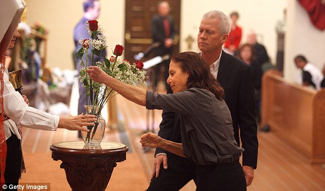 Always remembered: Ross Zimmerman and wife Pamela make a flower offering in honour of son Gabe during an interfaith memorial service held at St Augustine Cathedral in Tucson