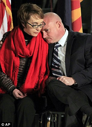 Lean on me: Giffords and husband Mark Kelly, who spoke to the crowd (left) and hugging Pam Simon who was also wounded in the attack