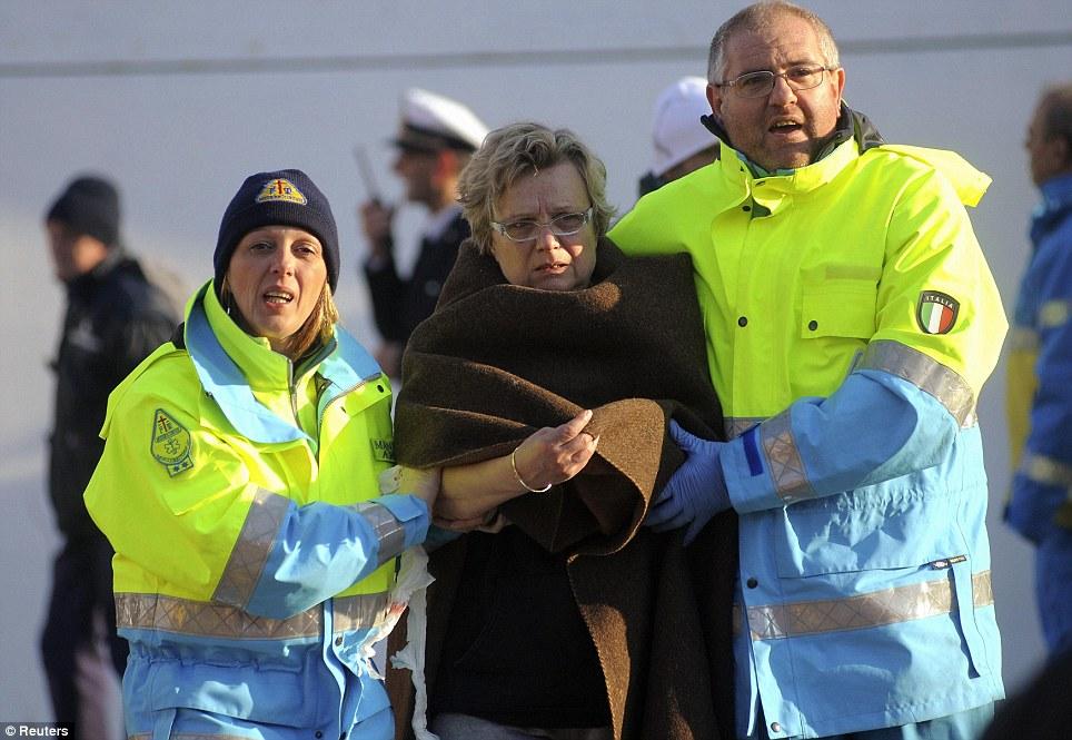 Les secouristes aider une femme comme elle est dirigée à la sécurité à Porto Santo Stefano.  Sauvetage avait de la difficulté de lancer