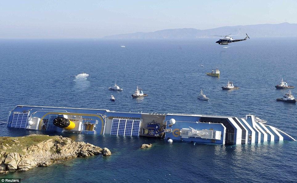 Le navire de croisière qui s'est échoué est observée au large de la côte ouest de l'Italie comme un hélicoptère au-dessus plane pour essayer de trouver des passagers