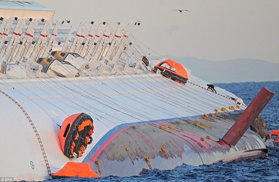 Membres des services d'urgence rampent le long du côté de la demi submergé bateau de croisière Costa Concordia que la recherche de survivants continuent