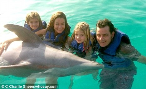 Family time: The short trip came after they also took a family holiday to the same destination around Christmas time, here they are seen swimming with the dolphins