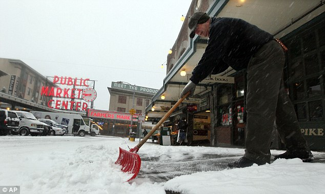 No business like snow business: Jeff Jarvis, facilities manager at the famous Pike Place Market, shovels snow at the landmark site