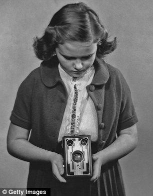 Una joven de tomar una fotografía con una caja de la cámara Kodak Brownie, circa 1935