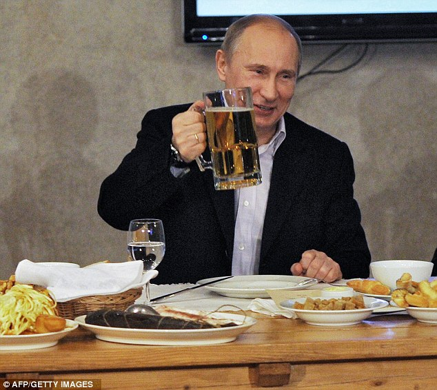 Leading the toast: Russian Prime Minister Vladamir Putin raises his glass at a meeting of football fans in St. Petersburg