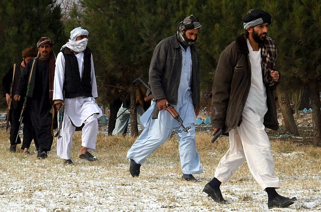 Abandoning their beliefs: The group of former Taliban members walk through a field ahead of the ceremony