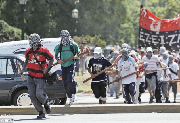 Masked members of Quebracho group, brandishing clubs, march to protest against Prince William's military posting