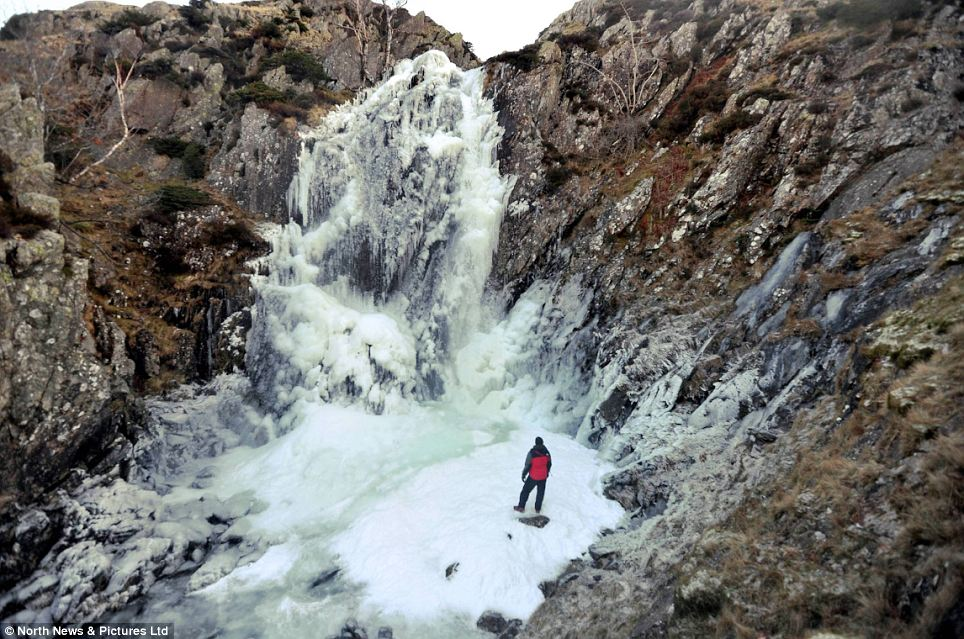 Frozen Britain: Fell walker Martin Campbell looks on at a frozen waterfall at Fisher Gill in the Lake District, after a severe frost brought the cascade to a standstill high on the Cumbrian fells