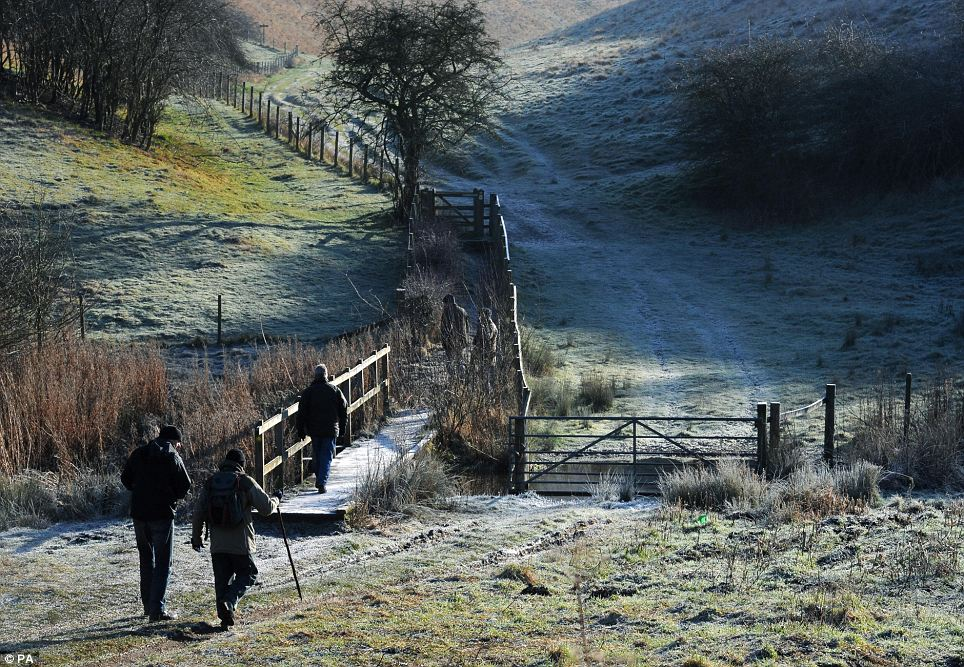 Err, great day for a ramble: Walkers make their way over the frozen ground in Millington Pastures, Pocklington, East Yorkshire