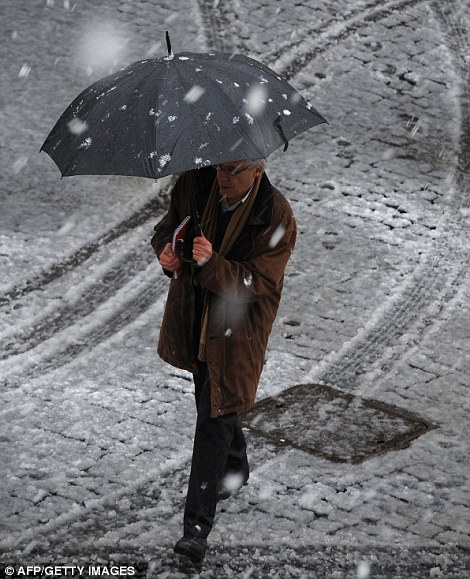 A man crosses a street as snow falls over Rome