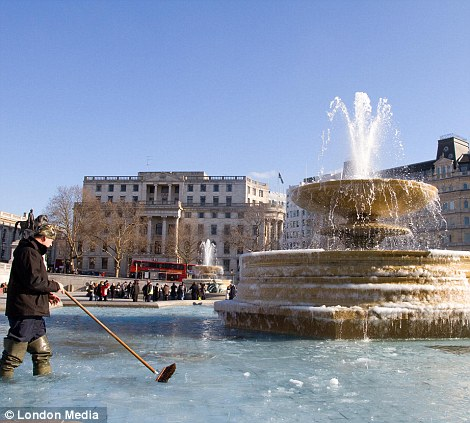 Council workers try and get London's Trafalgar Square fountains working properly after they froze in cold weather