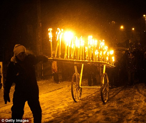 Chariot of fire: Torches are carried at the front of the procession, through the snow in Marsden, near Huddersfield