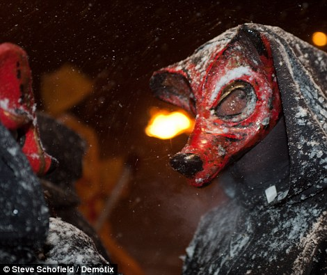 Braving the elements: Masked pagan performers prepare for their role in the fire festival - and get a dusting of snowflakes in the process
