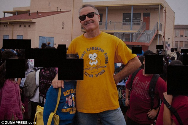 Posing: Berndt stands with a pupil among dozens of others while he wears a yellow Miramonte t-shirt