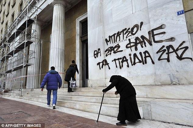 Los tiempos difíciles: una anciana mendiga por el Banco de la sede de Grecia en Atenas hoy