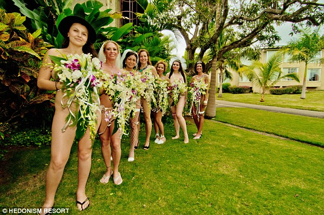 Exhibitionists: Seven of the brides cover their modesty with orchid bouquets at the Hedonism II resort in Negril, which held the group ceremony