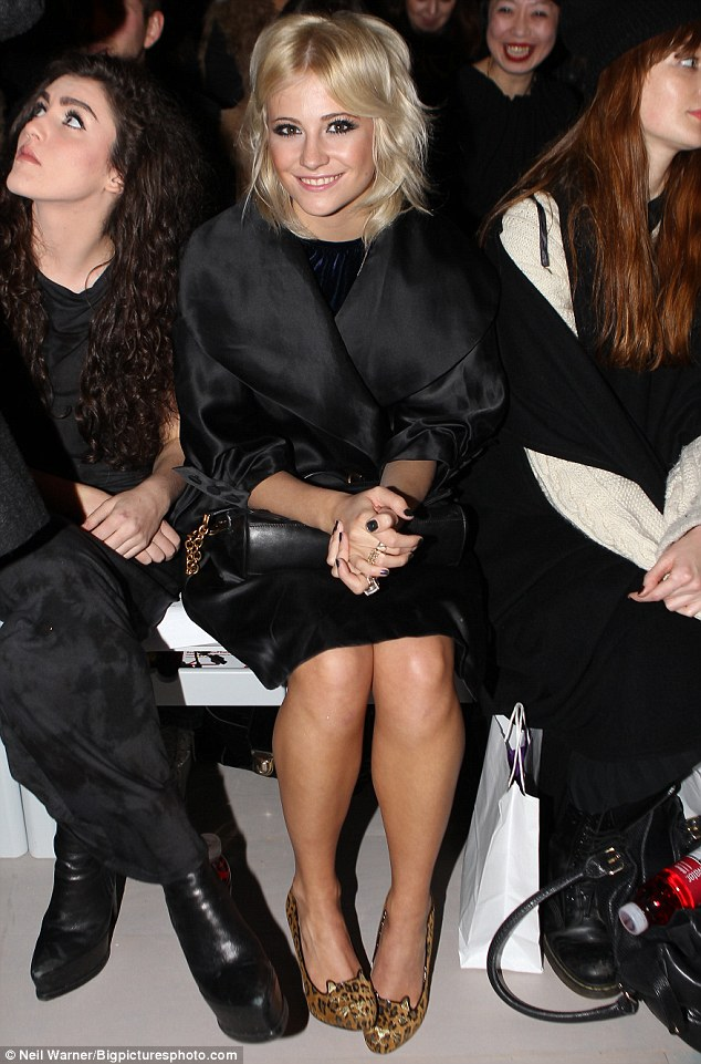 Back to black: Pixie looked very chic in her shiny black coat and leopard heels with cat ears