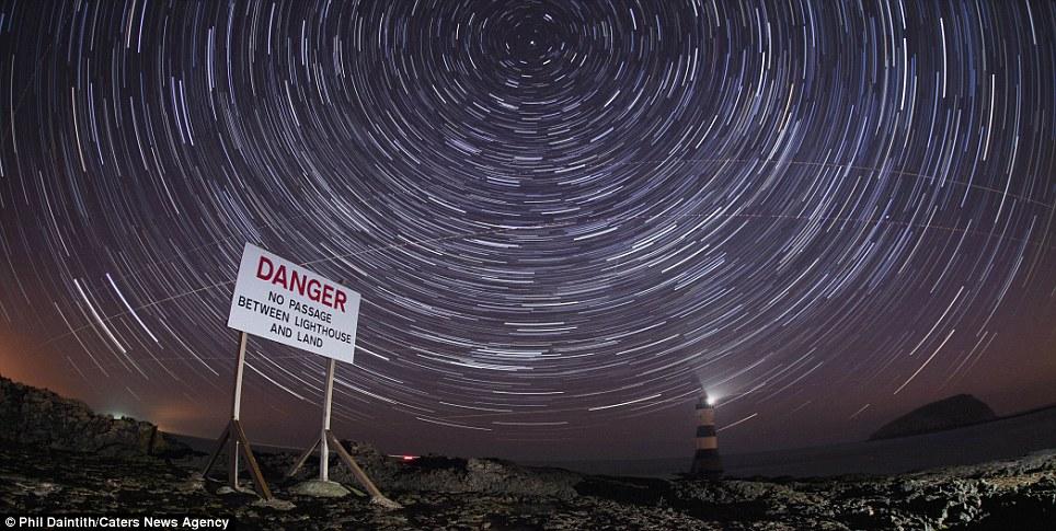 Peligro: Una señal de peligro con un faro en el fondo en Penmon en la costa de Angelsey al norte de Gales