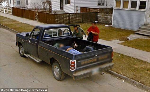 Bad timing? What could be a body is seen in the rear of this pick-up truck as the car goes by in Winnipeg, Canada