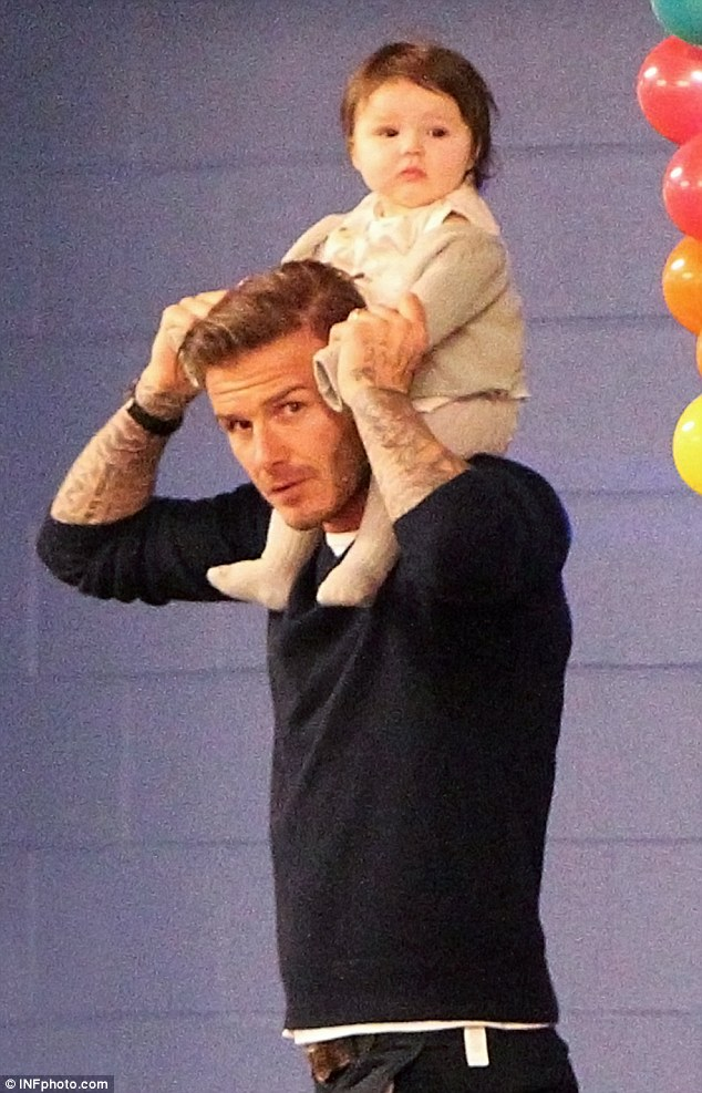 Cheer up cherub: David Beckham carries Harper at the Lucky Strike Lanes to go bowling for Cruz's 7th birthday