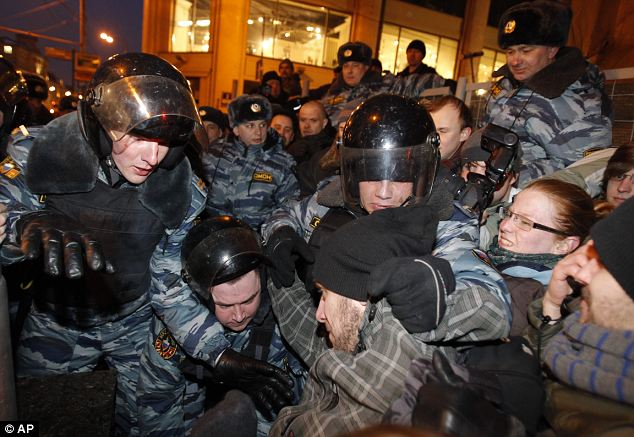 Unrest: Russian riot police grapple with demonstrators attempting to hold an unsanctioned protest in Moscow against the election result on Monday. An opposition group has claimed there were widespread violations in Sunday's ballot