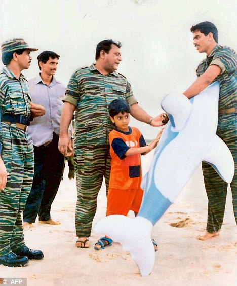 Tiger leader Prabhakaran (pictured) plays with his son Balachandran and LTTE comrades on a beach