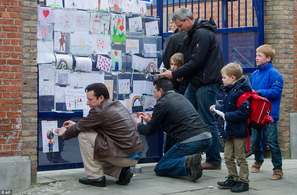 Heart wrenching: Teachers at St Lambertus attach drawings of pupils at the school gate on Wednesday morning
