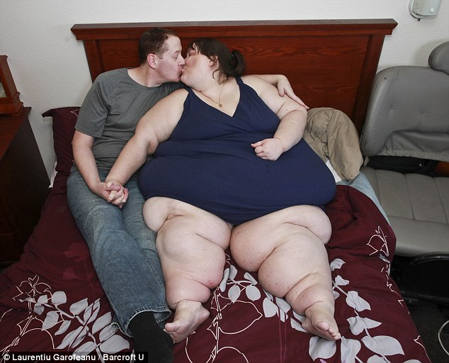 Love: Susanne and Parker share a kiss on their bed.