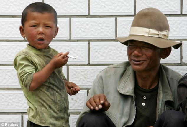 Young Chinese smoker: An boy smokes a cigarette, which he had asked from the man next to him, at Sangke grassland in Xiahe, western China's Gansu province - China is one of the countries that Mayor Bloomberg is hoping to target