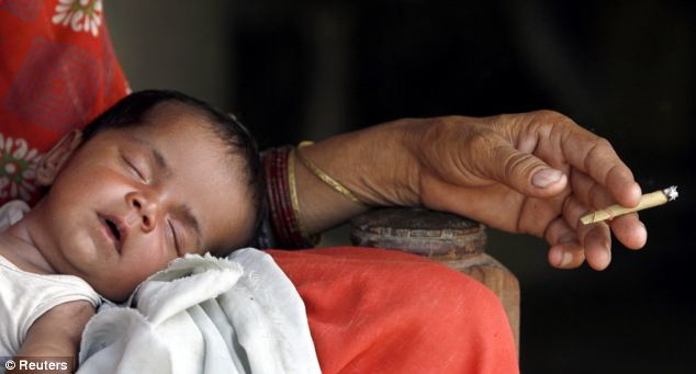 New born baby: India is also one of the places the mayor hopes will change from his donation - in this photo a smokes as she rests with her newly-born child in Akhera village in the northern Indian state of Haryana