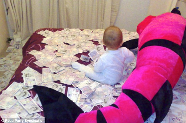 Too young to know: The baby in the picture is the child of thief Adu Bunu - from Bacau - who was jailed in 2008 for a hole-in-the wall scam estimated to have netted more than £1million