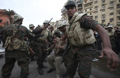 A pro-Mubarak supporter apprehended by opposition demonstrators is led away by the army during rioting near Tahir Square in Cairo in February last year
