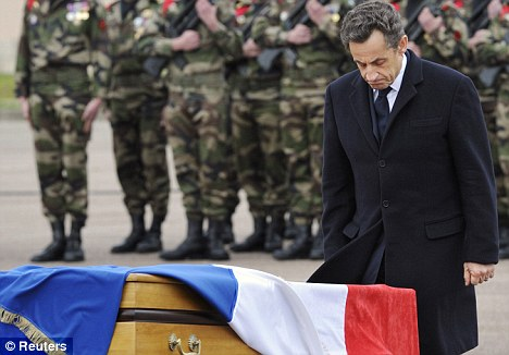 Paying his respects: Nicolas Sarkozy stands in front of one of the coffins of the three soldiers killed by Mohammed Merah in Toulouse last week