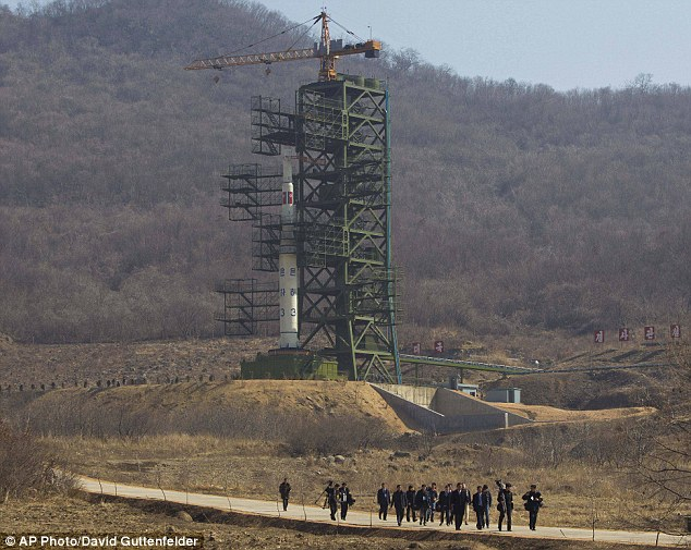 A group of journalists walk down a road in front of North Korea's Unha-3 rocket which it is expected to fire in the middle of April
