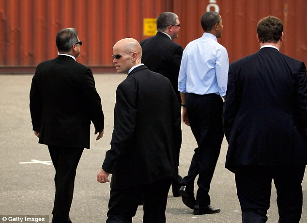 President Barack Obama (blue shirt) surrounded by Secret Service agents walks away after a visit to the Port of Tampa, Florida on his way to the Summit of the Americas in Colombia earlier today