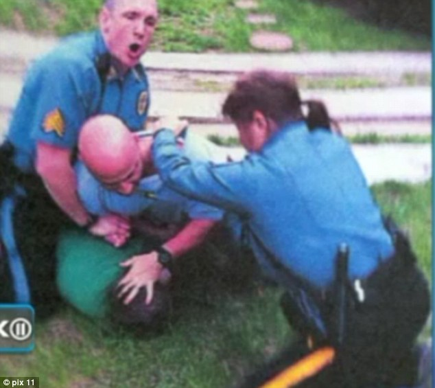 Breaking it up: This photo was taken by the teenage boy's distraught mother as she begged the policemen to stop hurting her son. Officer Regina Tasca is seen her trying to pull one of the men off - it was this intervention which may cost her, her job