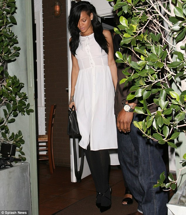 Making modest sexy: Rihanna livened up her white shirt dress at dinner last night with a pair of sexy suspender tights