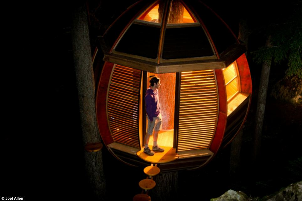 Joel Allen stepping into the amazing treehouse he built on public land in Canada at night