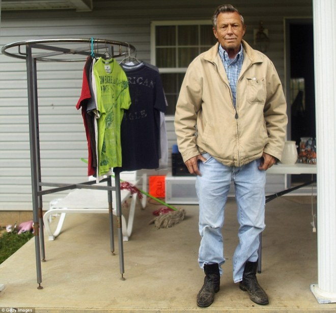 Willis Little poses next to items he has available for sale on his front porch on April 20 in Booneville