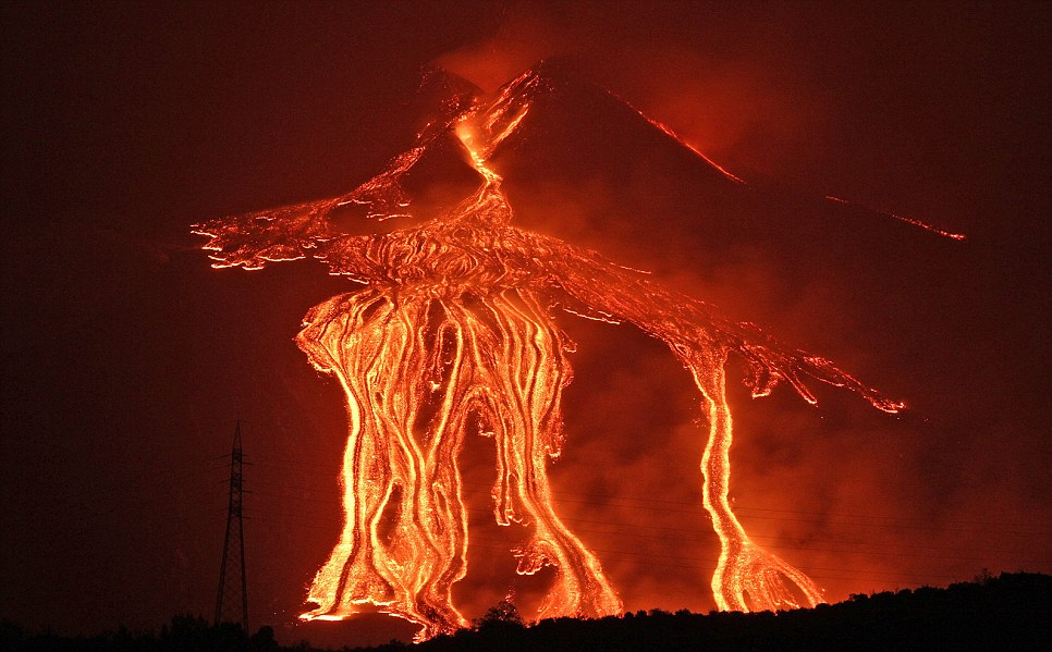 Spewed forth: The fiery fingers cascade down the side of Etna after it erupted again today
