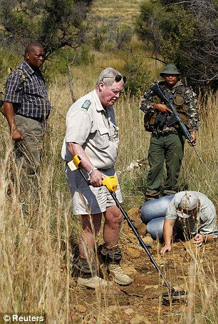 Conservationists and police investigate the scene of a rhino poaching incident on April 19